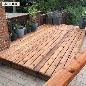 Byg-selv træterrasse med materialer fra GroundPlug® komplet byg-selv terrassepakke med træ af brunt fyrretræ.